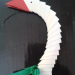 13. Теперь нам понадобиться 21 модуль белого цвета и один модуль красного для создания шеи и клюва. Для клюва я использовала обычную цветную бумагу красного цвета. Клюв получается раздвоенный, поэтому при желании Вы можете его склеить. Берем два модуля и вставляем уголки одного в кармашки другого. Собираем таким образом все детали и выгибаем в виде шеи. | Оригинал: http://svoimi-rukami-club.ru/модульное-оригами-лебедь-из-модулей/