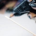Первым делом придайте фактурность будущей волшебной палочке. Для этого начните покрывать поверхность китайской палочки клеем из пистолета. В этом шаге покройте клеем только основание палочки. При этом располагайте клей в хаотичном порядке.